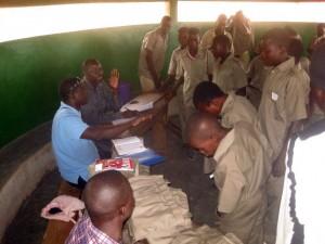 Nandji Tantar, im blauen Hemd, verteilt die Schulkleidung